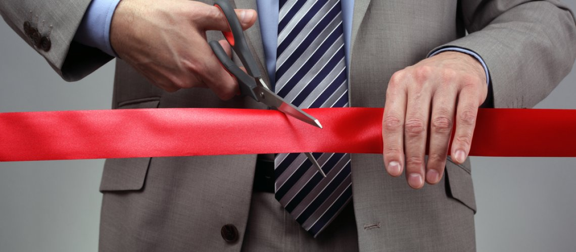 Cutting a red ribbon with scissors concept for new business venture or opening ceremony